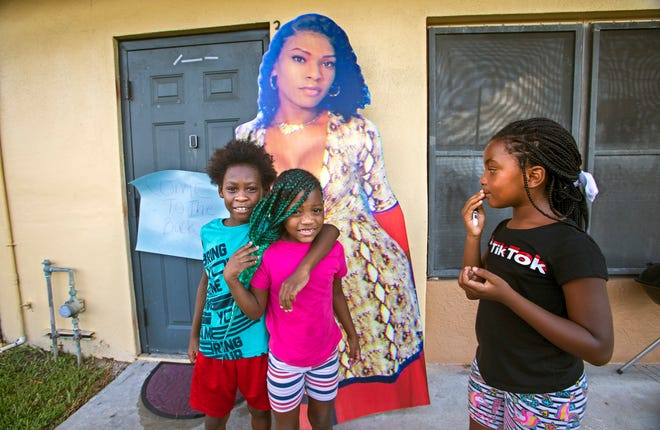 Pattron Oneal, 9, stands by a poster of Bee Love Slater Saturday with Carrie Williams, 6, and Kimmy Johnson, 8, at a memorial gathering for Bee Love at her family's home in Pahokee. It was partly a celebration of Bee Love and partly an awareness raising event for the many transgender women killed in the past two years in the United States. [LANNIS WATERS/palmbeachpost.com]