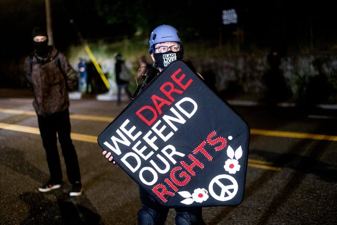 Stacy Kendra Williams holds a shield while facing off against police at the Penumbra Kelly Building on Thursday in Portland.