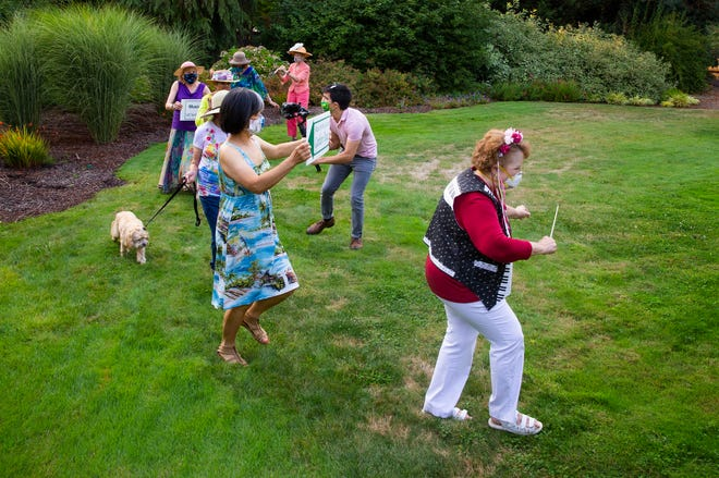 Members of the Eugene Symphony Guild march around the yard of fellow member Sally Robinson as Deej Martinez photographs. The group came together last week to create a video for the 2020 EUG Parade/Pet Promenade, which has gone virtual this year.
