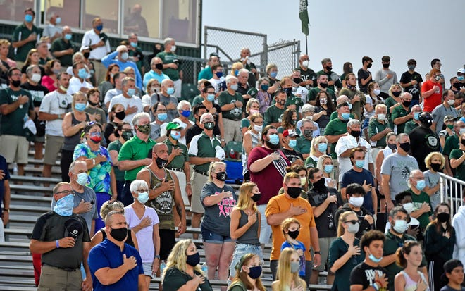 Mask-wearing fans stand for the National Anthem prior to Friday night's high school football game between IMG Academy National and Venice High at Powell-Davis Stadium in Venice.