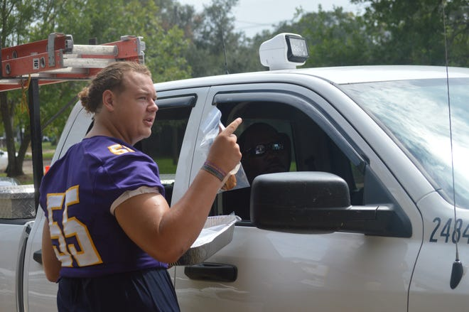 Alexandria Senior High senior offensive lineman Dylan Dauzart talks to a utility worker from the City of Alexandria while passing out food Saturday.