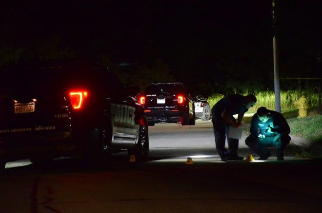 Crime lab investigators at the scene early Saturday.