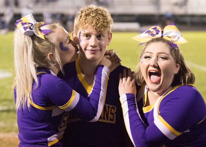 Unioto junior cheerleader Blaine Sealey blushes as he gets a kiss from female cheerleaders Dayna Lowman and Lauren Shoemaker as Unioto started to close the gap against Adena. Adena defeated Unioto Friday night in Chillicothe, Ohio, 34-6 on Sept. 4, 2020.