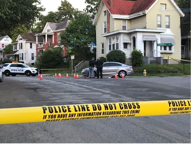 Officers on the scene of a shooting in Walnut Hills Sept. 4, 2020, examine a car riddled with bullet holes.