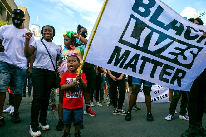 Ayden Wakefield, 3, holds a Black Lives Matter flag during a march on the 100th day of protests for Breonna Taylor in downtown Louisville Friday, September 4, 2020. Ayden's cousin Gerriona Board, 13, left and his sister Ayannay, Wakefield, 7, stand with him. Ayden's father, Allen Wakefield calls him 'the protest baby'.