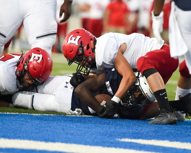 Roosevelt's Jaden Kroger (1) looks out from under East tacklers to see if he has crossed the goal line on Friday, Sept, 4th, 2020 during a game between the East Scarlets and the Roosevelt Roughriders at Drake University.