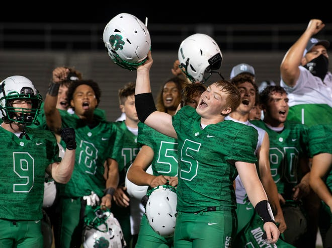 Ethan Brawdy (5) and North's football team celebrate by signing the school song after the Huskies' 14-7 victory over Castle on Aug. 21 at Bundrant Stadium.