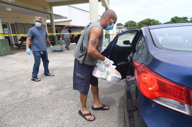 Jerome Espinosa, front, and other community maintenance workers, combine their efforts to pass out emergency food commodities to village residents during a drive-through distribution at the Agana Heights Mayor's Office on Saturday, Sept. 5, 2020.