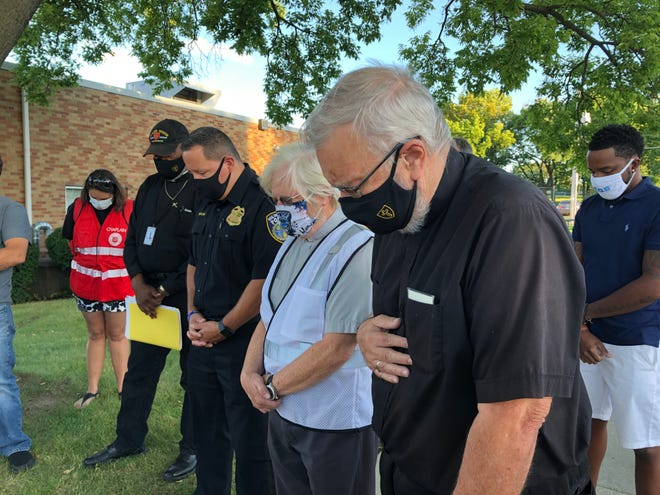 Police officers and community members bow their heads in prayer Friday for Milwaukee community service officer Naeem Sarosh, who was killed on Monday.