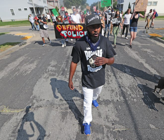 Community organizer Khalil Coleman leads a group supporting The Peoples Revolution as they march from Johnsons Park on West Fond du Lac Avenue through the streets of Milwaukee  on Sept. 5, 2020. The group marked their 100th day of marching since widespread protests began in Milwaukee on May 29, four days after George Floyd, a Black man, died when whiteMinneapolis Police Officer Derek Chauvin knelt on his neck for nearly nine minutes during an arrest.
