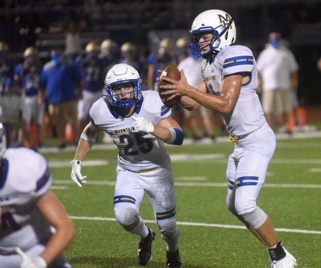 Mountain Home's Gage Hershberger (25) prepares to take a handoff from quarterback Bryce McKay during the Bombers' 48-34 loss to Harrison on Friday night.
