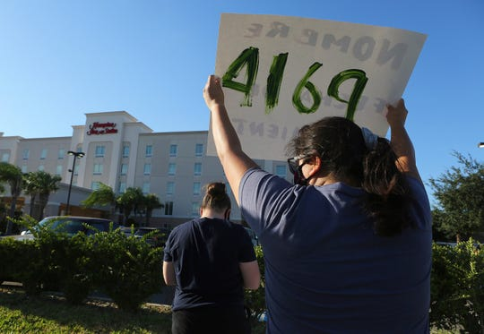 In this July 23, 2020, file photo, protesters wave signs in front of the Hampton Inn hotel in McAllen, Texas. The Trump administration has sharply increased its use of hotels to detain immigrant children as young as 1 before expelling them from the United States during the coronavirus pandemic despite facing outcry from lawmakers and human-rights advocates. (Joel Martinez/The Monitor via AP, File)