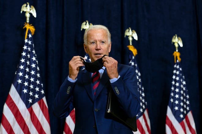 Democratic presidential candidate former Vice President Joe Biden puts on his face mask after speaking to media in Wilmington, Del., Friday Sept. 4, 2020. (AP Photo/Carolyn Kaster)