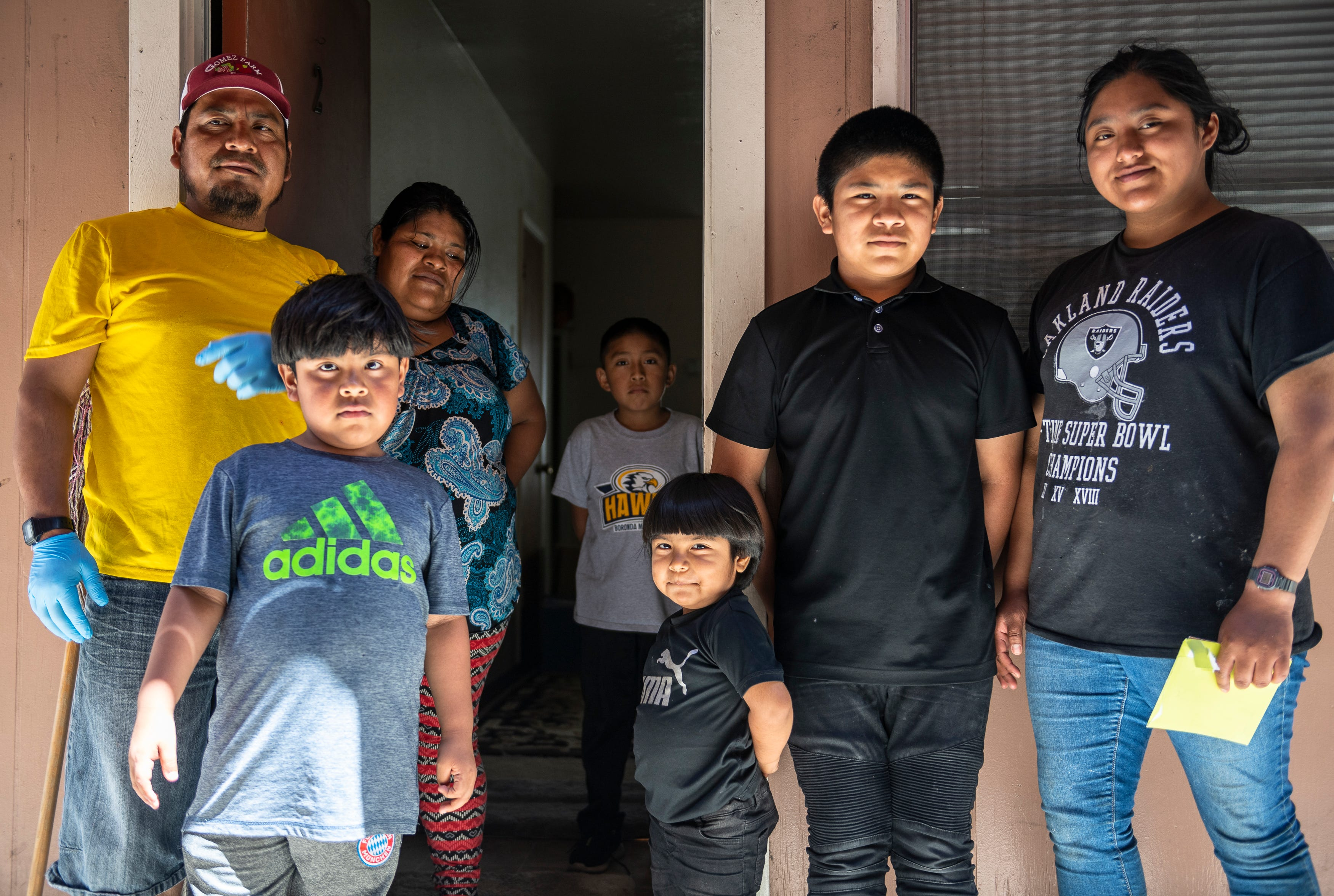 Resi Salvador (right), stands outside of her family's apartment in Salinas, Calif., with her three brothers, family friend, stepmother, and father.