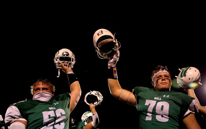Wall High School football players Luke Lipsey (56) and Tate Williams (79) celebrate a win over Cisco at Hawk Stadium on Friday, Sept. 4, 2020.
