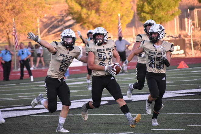 The Desert Hills defense celebrates a Cy Nunely (21) interception against Pine View Friday.
