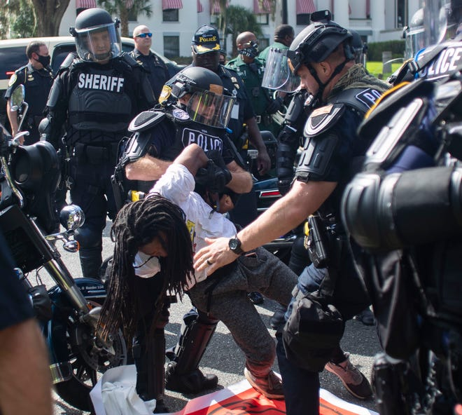Law enforcement officers take several Black Lives Matter protesters into custody during a peaceful march Saturday, Sept. 5, 2020.