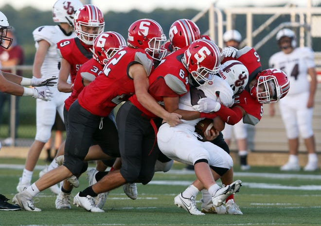 A host of Generals, including Shay Taylor (5) Cahse Young (64) and Eli Gordon converge on John Glenn's Noah Wellmeier.