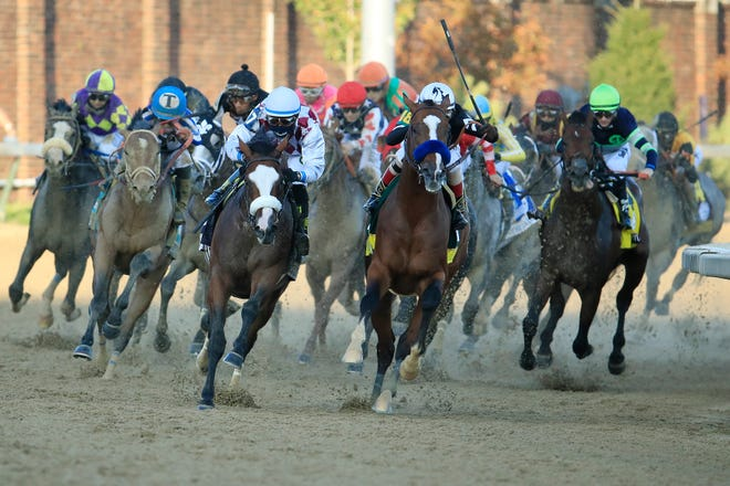 Authentic #18, ridden by jockey John Velazquez leads the field into the final turn.