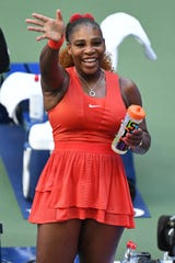Serena Williams waves to her daughter Olympia in the stands after her match against Sloane Stephens.