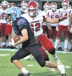 Bartlesville High School receiver Gage Keaton, left, zips toward daylight while Claremore High pass rusher Kade Steelmon approaches from backside pursuit during last Friday's season football opener at Custer Stadium. Bartlesville won, 34-10.