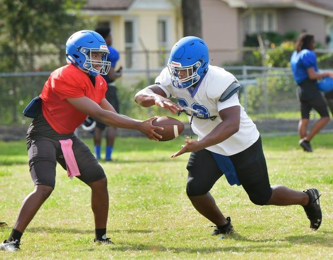 Lee quarterback Cale Zarah (left) hands off to running back Zaire Lee during practice Wednesday.