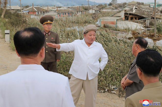North Korea leader Kim Jong Un talks to officials Saturday as he visits a damaged area in the South Hamgyong province, North Korea, following a typhoon known as Maysak. Independent journalists were not given access to cover the event depicted in this image distributed by the North Korean government. The content of this image is as provided and cannot be independently verified.