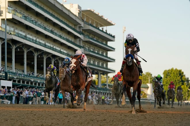 Jockey John Velazquez riding Authentic, right, crosses the finish line Saturday to win the 146th running of the Kentucky Derby at Churchill Downs in Louisville, Ky.