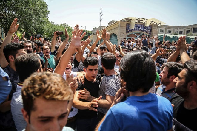 A group of protesters chant slogans at the main gate of the Old Grand Bazaar, in Tehran, Iran, in June 2018. On Saturday, Iran broadcast the televised confession of a wrestler facing the death penalty after a tweet from President Donald Trump criticizing the case, a segment that resembled hundreds of other suspected coerced confessions aired over the last decade in the Islamic Republic. The case of 27-year-old Navid Afkari has drawn the attention of a social media campaign that portrays him and his brothers as victims targeted over participating in protests against Iran's Shiite theocracy in 2018.