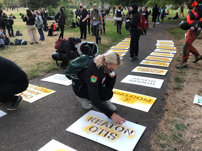 Protester Chelsea Jordan spray paints the names of slain Black men at a city park Saturday as protesters gathered for the 100th straight day against racism and police brutality in Portland, Ore.