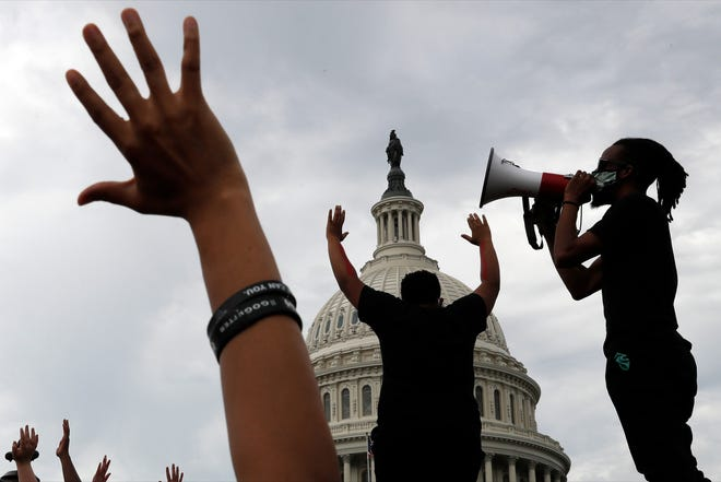 Demonstrators protest the death of George Floyd in June as they gather on the East side of the U.S. Capitol in Washington. Floyd died after being restrained by Minneapolis police officers. The three month stretch between the symbolic kickoff and close of America's summer has both galvanized broad public support for the racial justice movement and exposed the obstacles to turning that support into concrete political and policy changes.