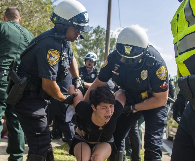 Law enforcement officers take several Black Lives Matter protesters into custody during a peaceful march Saturday, Sept. 5, 2020, in Tallahassee, Fla. The protest was in response to a grand jury opting not to charge Tallahassee police officers in the deaths of three Black suspects in separate incidents earlier this year.  (Alicia Devine/Tallahassee Democrat via AP)