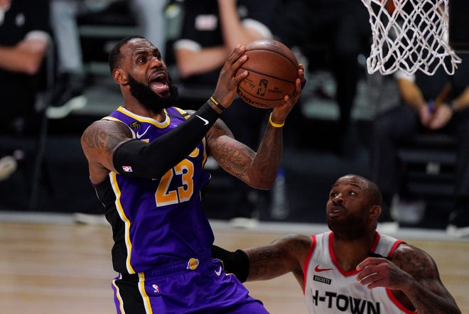Los Angeles Lakers' LeBron James (23) drives to the basket over Houston Rockets' P.J. Tucker during the second half of an NBA conference semifinal playoff basketball game Friday, Sept. 4, 2020, in Lake Buena Vista, Fla. (AP Photo/Mark J. Terrill)