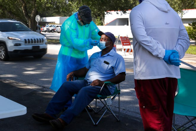 Eduardo Garcia, a registered nurse with the Florida Covid-19 Mobile Testing Lab, tests a patient outside of the Martin Luther King Jr. Multipurpose Center in Gainesville, Fla. on Sept. 5, 2020. [Sam Thomas/The Gainesville Sun]