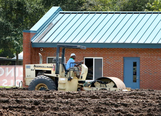 A construction worker uses a steam roller to level dirt as construction continues at Metcalfe Elementary School in Gainesville on Thursday.