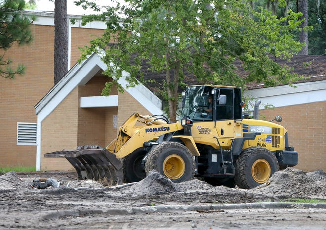 A construction worker uses a front-end loader to grade the dirt as construction continues at Howard Bishop Middle School in Gainesville on Thursday. Several schools in the Alachua County Public Schools District are under major construction.