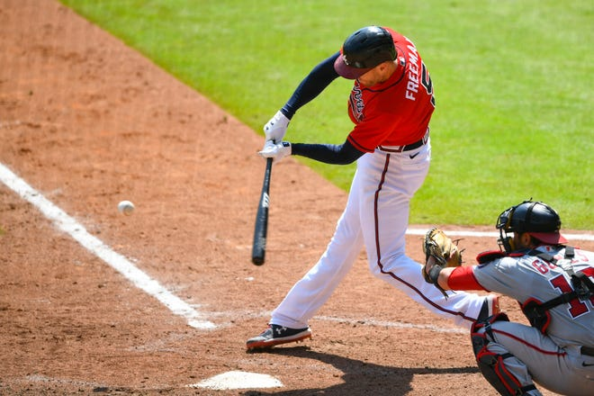 The Atlanta Braves' Freddie Freeman connects for a grand slam over left center field during the sixth inning of Sunday's game against the Washington Nationals.