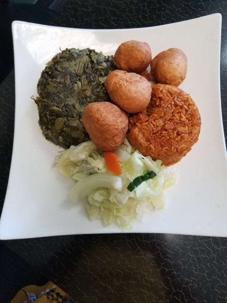 An African dish featuring jollof rice, greens and cabbage at A&H African & Jamaican Restaurant in Lindenwold.