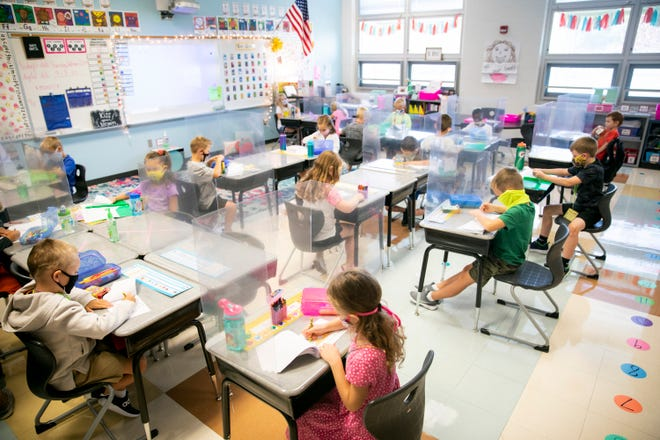 Mrs. Priore's first grade class practices coloring before the morning announcements at Three Rivers School Elementary in Cleves on Friday, September 4, 2020. The desks are staggered throughout the classroom to provide more space between students.
