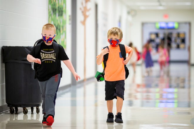 Kindergartners walk to their classroom at Three Rivers School Elementary in Cleves on Friday, September 4, 2020. All students, faculty and staff must wear a mask while in the school buildings.