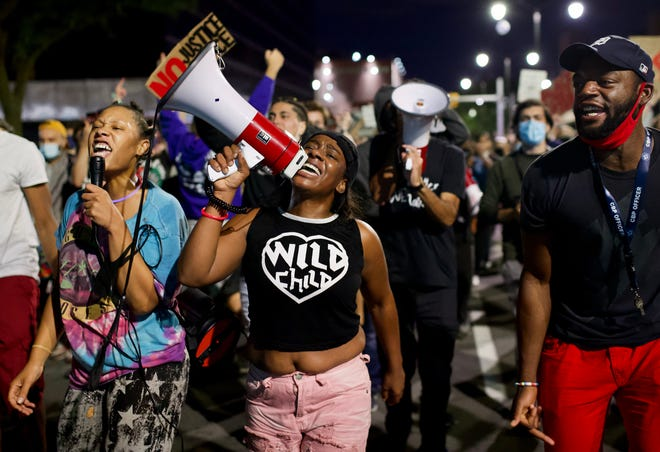 Adrian Johnson left and Shaqualla Johnson, center lead chants as protesters march on St Antoine as Detroit Will Breathe marked their movement's entrance into triple-digit days of protesting in Detroit, August 5, 2020.