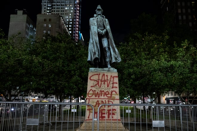 """The Gen. Alexander Macomb monument on Michigan Avenue at Washington Boulevard in downtown Detroit defaced with """"Slave owner"""" and """"land thief""""  spray painted on the base on Saturday, Sept. 5, 2020."""