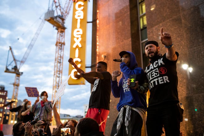 Detroit Will Breathe protesters include Jae Bass, center left, Ethan Lucas, right, chant Black Live Matter as they stand on top of outdoor dinning fence of Calexico Detroit restaurant in downtown Detroit, Saturday, Sept. 5, 2020.