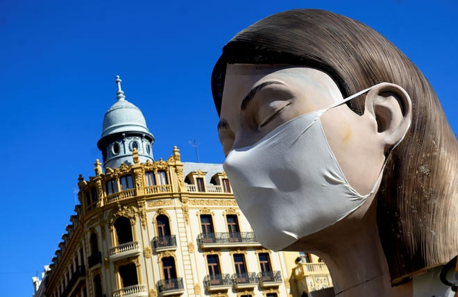 "A ""ninot"", a gigantic structure made of cardboard portraying current events, wearing a protective mask is displayed in Valencia on March 11, 2020 after the Fallas festival was cancelled over the coronavirus outbreak. (Photo by Jose Jordan/AFP via Getty Images)"
