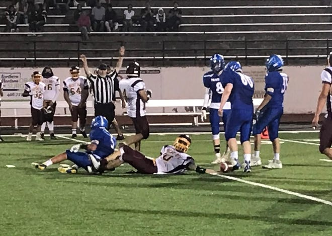 Rocky Boy's Kellen Colliflower (10) reaches just far enough over the 25-yard line to get a first down during the Stars' game against Great Falls Central. Dillon Warren (5) was in on the tackle.