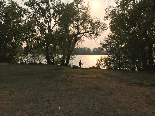 An angler fishes on the Missouri River at Broadwater Bay in Great Falls Sunday as under a hazy sky filled with smoke from fires burning in northern California.