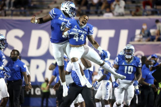 Memphis Tigers defender Xavier Cullens, left, celebrates his interception along the sidelines with teammate Kendell Johnson.