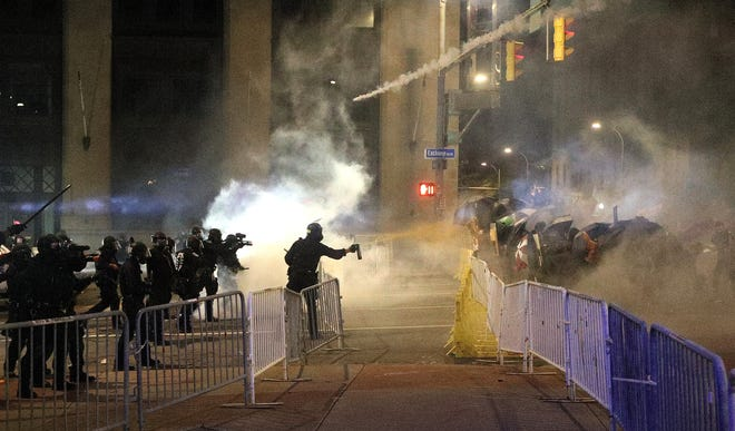 Police spray pepper spray along with tear gas into a large group of demonstrators at the corner of Broad St. and Exchange Blvd in downtown Rochester.