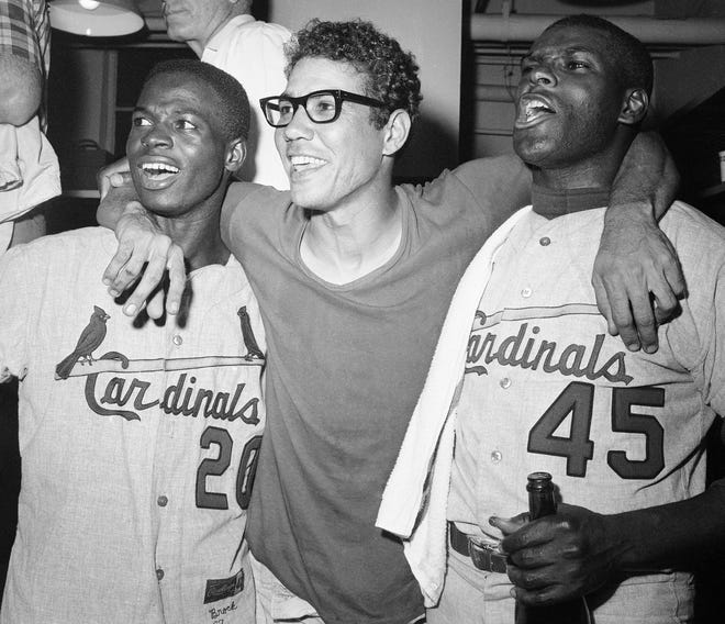St. Louis Cardinals' heroes of the final game of the 1967 World Series, Lou Brock (left) and pitcher Bob Gibson (right) are embraced by teammate Julian Javier following their 7- 2 victory over the Boston Red Sox to win the 1967 World Series on Oct. 12, 1967 at Fenway Park. Brock set a Series record of seven stolen bases.