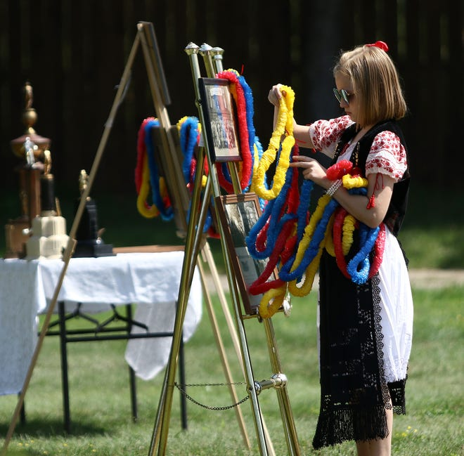 Livia Farian, one of the youngest society members, places garlands in the colors of the Romanian flag on pedestals holding historic photos of the society before the start of Sunday's monument dedication ceremony for the Unirea Romana Transilvaneana Society (United Romanians of Transylvania) at the Alliance City Cemetery. Ed Hall Jr., Special to The Alliance Review